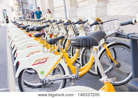 MILAN, ITALY - AUGUST 15, 2016: Bikes parked in racks to be used as public sharing service. Named BikeMi, it s the first example in the world of an integrated bike sharing system.