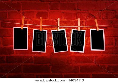pictures or photographs on a rope with clothespins, with clipping path for images, in front of a brick wall