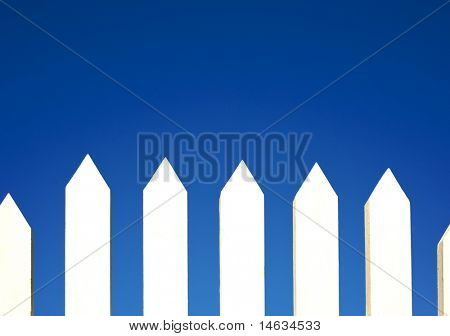 A white picket fence background in front of a bright blue sky with copy space.