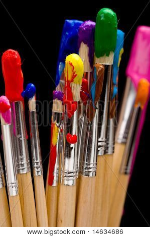 A group of multi-color painbrushes on a black background