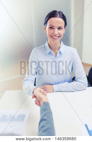 business and office concept - smiling businesswoman shaking hand in office