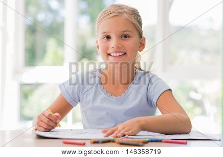 Portrait of a cute little girl drawing on table. Happy little girl coloring with crayons and looking at camera. Little child girl smiling and looking at camera.