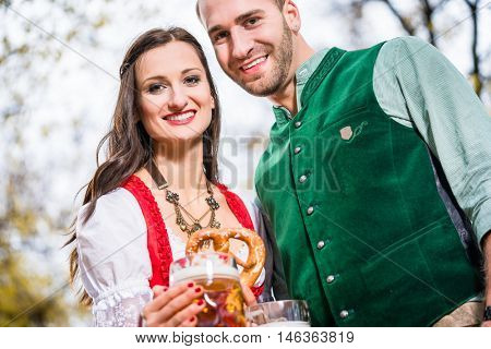Man and woman in bavarian Tracht having a Pretzel an beer in a mug