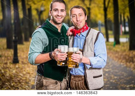 Two men in Bavarian Tracht, clinking glasses with a Mass Bier