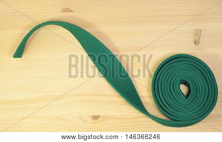 Aikido green belt on wooden background. Close up