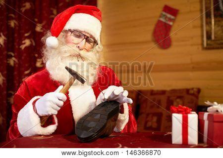 Santa Claus repairing shoe at the table