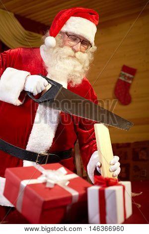 Santa Claus making presents himself