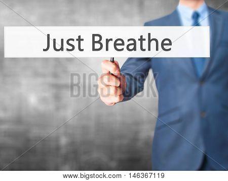Just Breathe - Businessman Hand Holding Sign