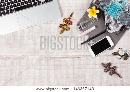 Fashion women accessories. Luxury handmade snakeskin (python) handbag, cosmetics, makeup accessories fashion set, frangipani flowers, laptop, smartphone, panties. Top view, flat lay, light wooden  background. Free/empty space for text. Stylish meeting set