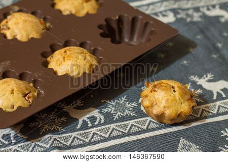 Salty muffins with sausage and cheese in silicone bakeware on gray tablecloth with deers.