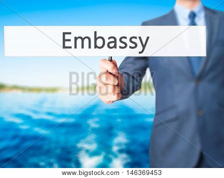 Embassy - Businessman Hand Holding Sign