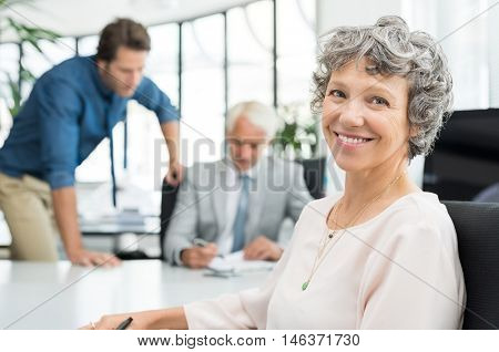 Close up face of executive businesswoman sitting in office while her team working in background. Portrait of smiling business woman looking at camera. Happy senior woman satisfied with her company.