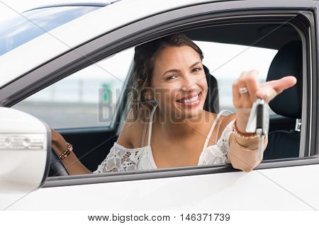 Multiethnic woman showing new car keys and car. Young smiling girl driving her new car and looking at camera. Portrait a young happy woman sitting in car holding car keys.