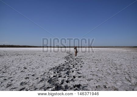 Girl standing on the dry bottom of a salt lake. Walk the dark-haired woman in a swimsuit on the bottom of a dry lake with salt and mud. The ancient dried-up lake.