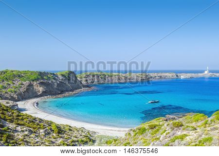 Cala Presili beach with the view on Raco de sAlga Morta and Faro de Favaritx on a sunny summer day, Menorca island, Balearic islands, Spain.