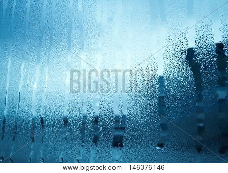 Window glass with condensation in early morning winter tone style on building and sky background