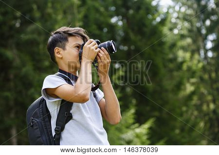 a young boy takes pictures in nature