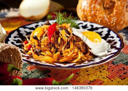 Asian Style Noodles with Meat and Laghman Sauce. Garnished with Fried Egg