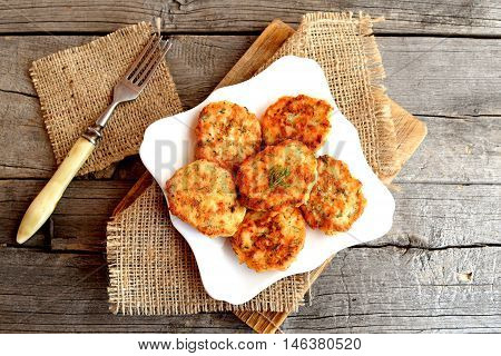 Fried fish cakes on a plate, fork on old wooden background. Cutlets from minced salmon. Delicious and nutritious lunch or dinner