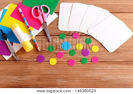 Cut cards and circle, scissors, pencil, glue stick, colored cardboard sheets on a wooden table. How to make educational flashcards for teaching kids color and account. Do it yourself. Step