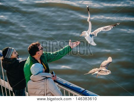 HELSINKI FINLAND - MARCH 17 2015: Happy family feeding seagulls on a ferry. Very friendly seagull takes food from man's hand.