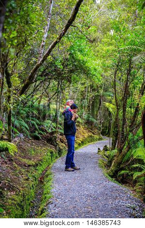 Father Is Carrying Little Daughter On His Shoulders. Haast, South Island, New Zealand