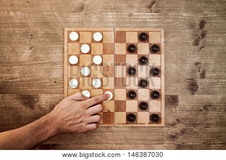Man starting play draughts checkers board game