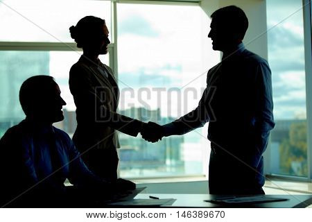 Two business people handshaking in the dark