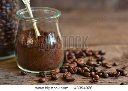 Ground coffee in a glass jar with coffee beans on a wooden background