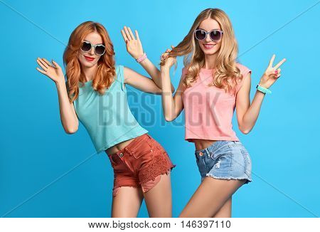 Fashion Hipster woman Having Fun Crazy Cheeky Dance. Hipster Sisters Best Friends Twins in Stylish Summer Outfit. Funny Model Girl Fashion Sunglasses.Glamour fashion Trendy Hairstyle, dancing.Creative