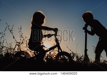 little boy and girl riding bike and scooter at sunset, active kids sport