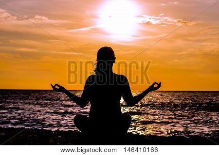 Female yoga lotos silhouette on beautiful beach during sunset. Tree Pose.