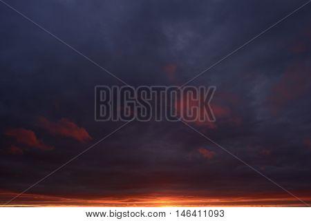 Dark blue cloudy sky in a fiery sunset light