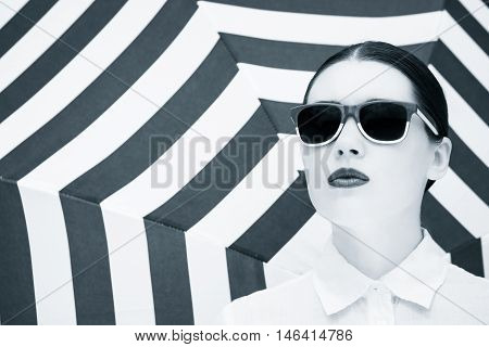 Portrait of a pretty young woman in colorful sunglasses next to striped background. Black and white