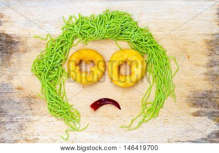 sad faces on wood background made from vegetable and noodle with space for your text.