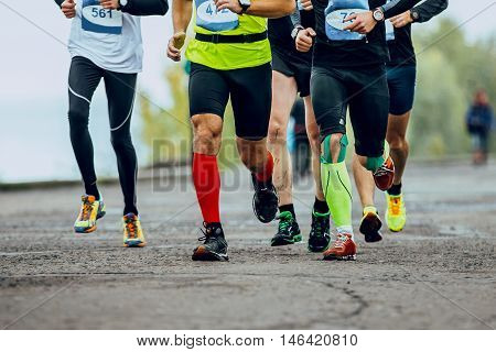 group of men runners running streets of city. legs compression socks. competition in marathon