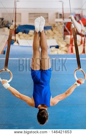 gymnast performs exercise rings. competitions in artistic gymnastics. athlete from back