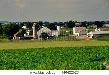 Lancaster County Pennsylvania - June 6 2015: A large Amish farm with barns silos sheds and the family home surrounded by fields of crops