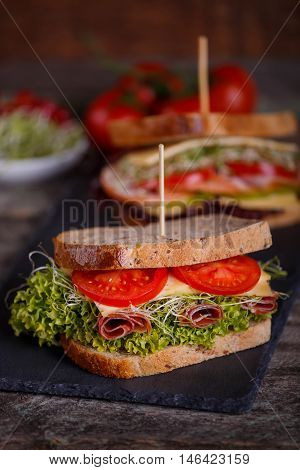 Two Sandwiches With Cereals Bread With Lettuce, Slices Of Fresh Tomatoes And Sweet Pepper, Ham, Pros