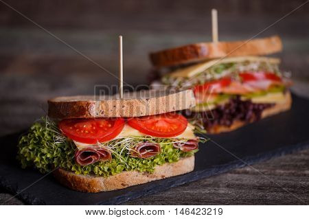 Two Sandwiches With Cereals Bread With Lettuce, Slices Of Fresh Tomatoes And Sweet Peper, Ham, Prosc