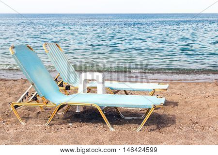 Two chaise longues on the sand of sea beach