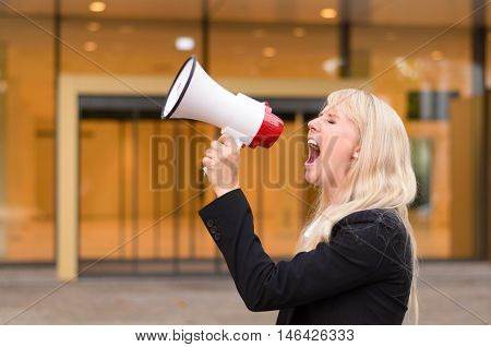 Angry young woman protester yelling into a megaphone sharing her grievances during a demonstration close up side view in an urban setting