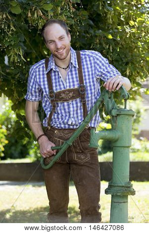 handsome man in traditional bavarian clothes standing next to an old water pump