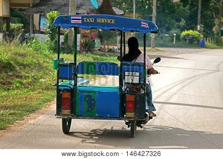 KRABI, THAILAND - MAY 2014 : Woman with black headscarf driving shuttle tricycle motorcycle taxi on street in Koh Lanta District in Krabi Province, Thailand on May 15, 2014.