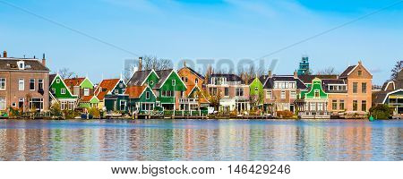 Panorama with row of old dutch green traditional houses in town Zaanse Schans in Netherlands, North Holland near Amsterdam