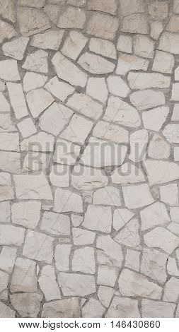 exterior decorative light gray old rough wall made of natural sandstone with potholes and streaks thick seams country-style vertically