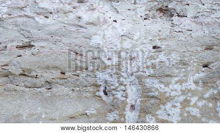 light gray old rough wall made of natural sandstone with potholes and smudges on the street