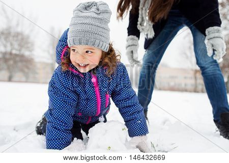 Unrecognizable mother with her cute little daughter building a snowman, playing outside in winter nature