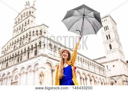 Young female traveler in yellow sweater and hat having fun with umbrella in front of San Michele basilica in Lucca old town in Italy. Having great vacations in Lucca