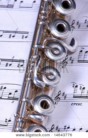 Silver flute instrument resting on a music score
